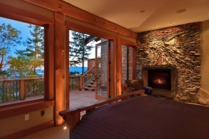 Log house master bedroom with feature fireplace