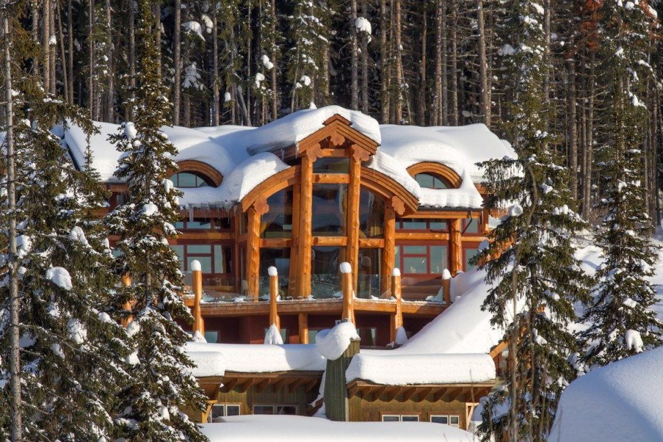 luxury log cabin covered in snow