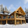 Outside of post and beam log home in the snow