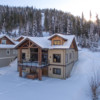 Side view of the outside of a timber frame log home in the snow