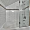 Glass shower and tile bathtub in timber frame log home bathroom