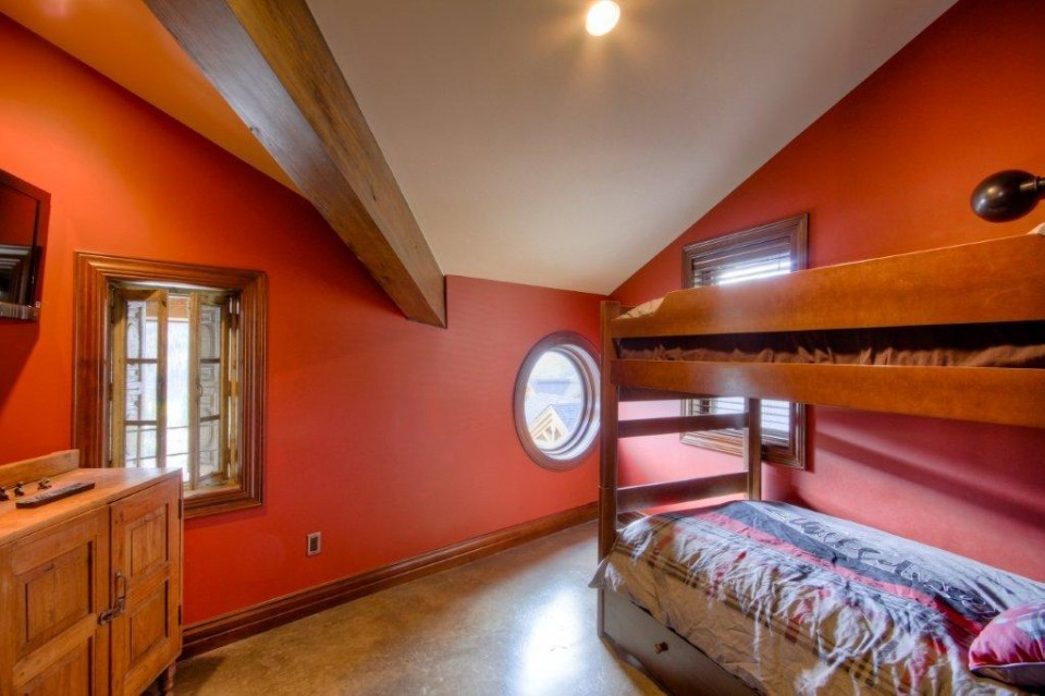 Kids room painted red with bunk beds