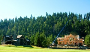 Log home under construction next to completed project