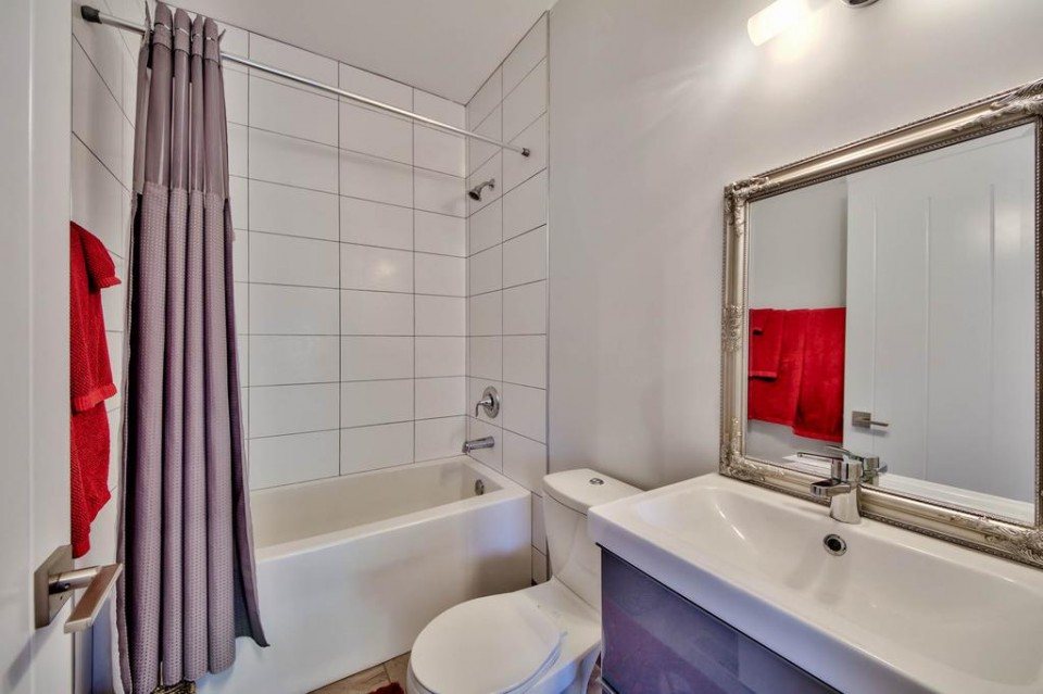 White bathroom with red accents in modern home