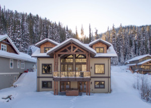 Outside view of a timber frame log home in the snow