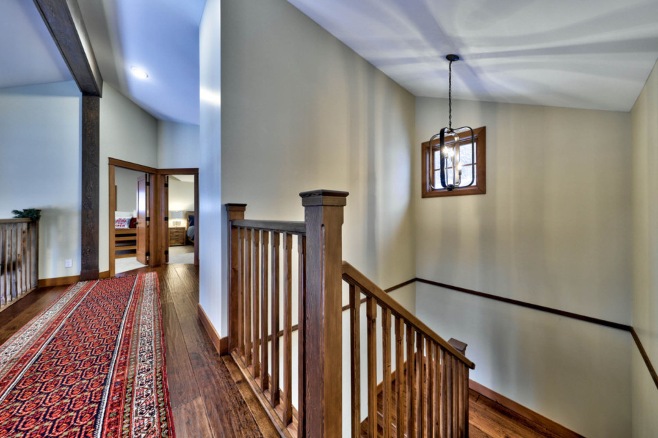 Lighting fixture at the top of the staircase in a timber frame log home