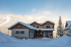 Outside entrance to a timber frame log home surrounded by snow
