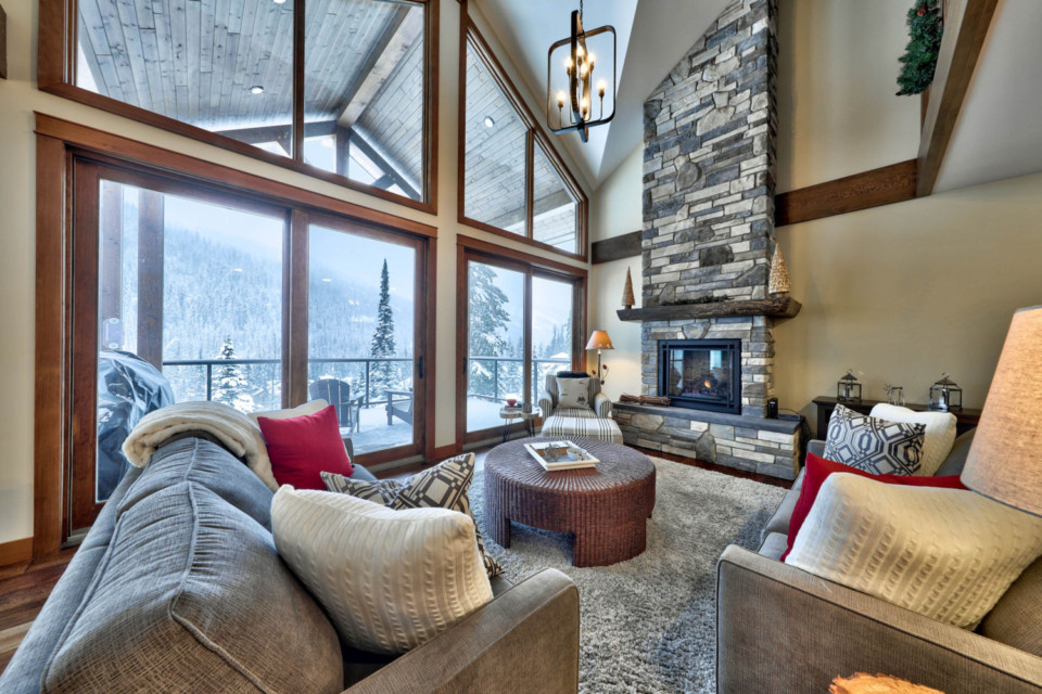 Grand room with large windows in a timber frame log home