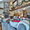 Grand room view of stone fireplace and loft area in a timber frame log home